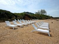 A Row Of Wooden Benches Sitting On Top Of A Sandy Beach